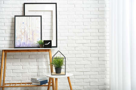Stylish room interior with pictures on table near brick wall. Space for text 版權商用圖片