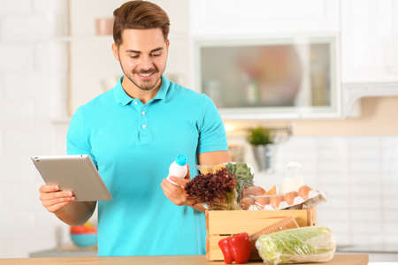Young man with tablet PC and products in kitchen. Food delivery service