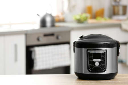 Modern electric multi cooker on table in kitchen. Space for text Stock Photo