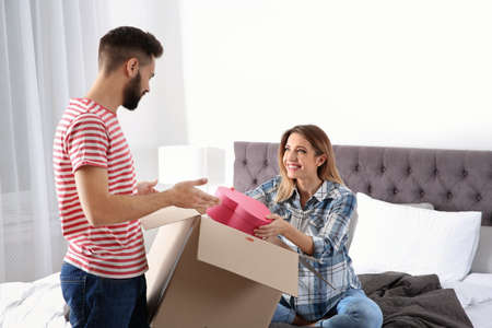 Young couple opening parcel in bedroom at home