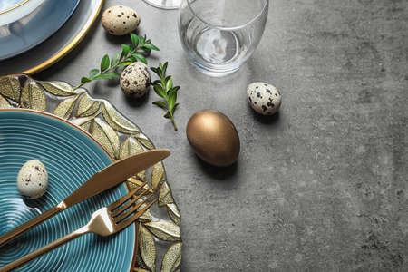 Festive Easter table setting with eggs on color background, above view. Space for text