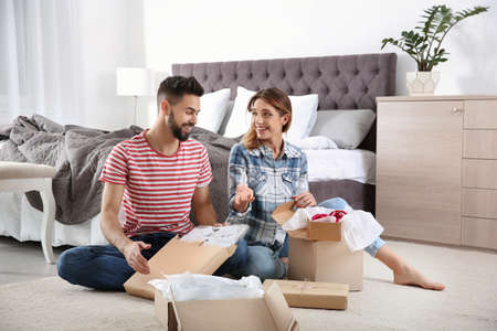 Young couple opening parcels in bedroom at home