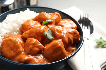 Delicious butter chicken with rice served on table Фото со стока