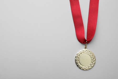 Gold medal with space for design on light background, top view. Victory concept Stock Photo