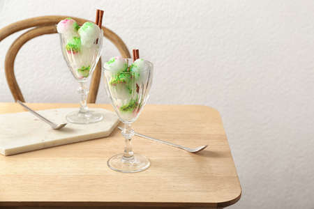Glasses with snow ice cream dessert on table against light wall. Space for text