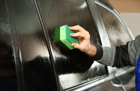 Worker washing tinted car window in shop, closeup