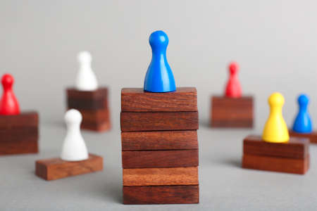 Board game piece on wooden blocks dominating other figures against grey background. Victory concept Imagens