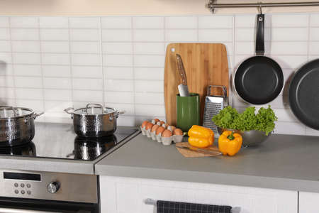 Set of clean cookware, utensils and products on table in modern kitchen