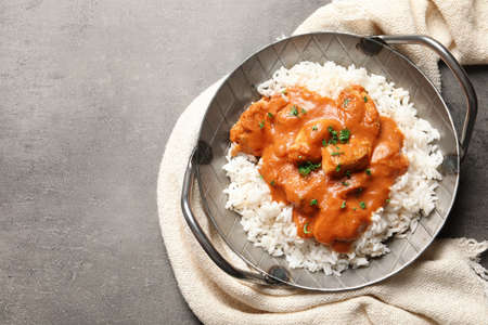 Delicious butter chicken with rice in dish and napkin on grey background, top view. Space for text