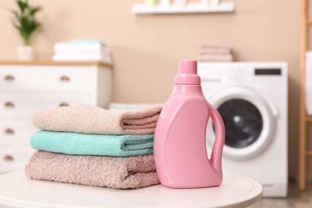 Stack of towels and detergent on table against blurred background Фото со стока