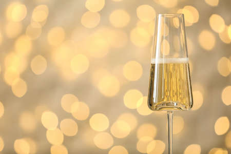 Glass of fizzy champagne against blurred fairy lights, space for text Banco de Imagens