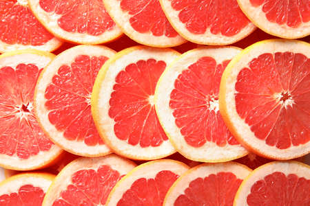 Many sliced fresh grapefruits as background, top view