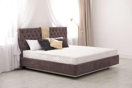 Comfortabel bed met nieuwe matras bij raam in de kamer. Gezonde slaap Stockfoto