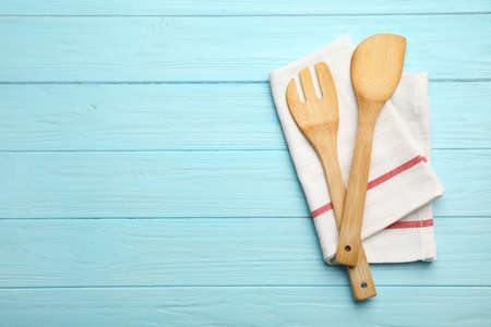 Wooden spatula, fork and napkin on color background, top view with space for text Imagens