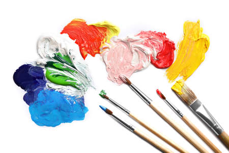 Paint strokes and different brushes on white background, top view