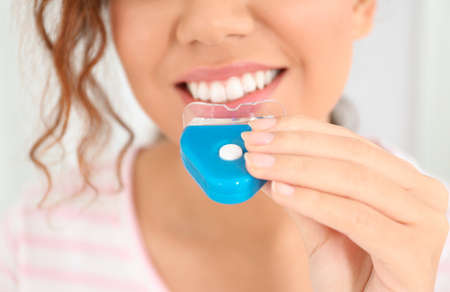 Young African-American woman using teeth whitening device on light background, closeup Banco de Imagens