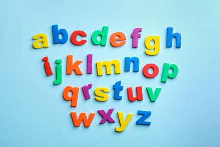 Magnetische Kunststoffbuchstaben auf farbigem Hintergrund, Ansicht von oben. Alphabetischer Reihenfolge