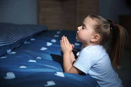 Little girl saying bedtime prayer near bed in room at night