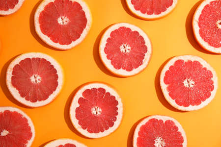 Fresh sliced ripe grapefruit on color background, flat lay 版權商用圖片
