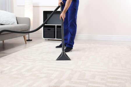 Hombre quitando la suciedad de la alfombra con aspiradora en interiores, primer plano