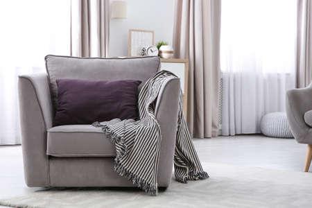 Wygodny fotel z miękką poduszką w nowoczesnym wnętrzu salonu. Miejsce na tekst