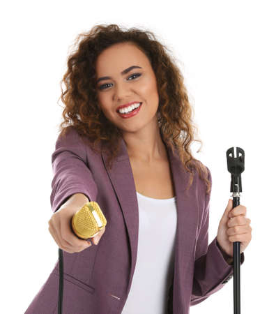 Curly African-American woman in suit with microphone on white background
