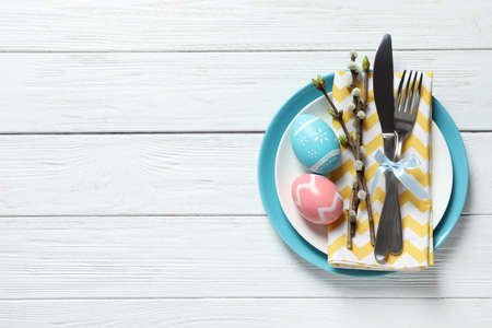 Festive Easter table setting with painted eggs on wooden background, top view. Space for text