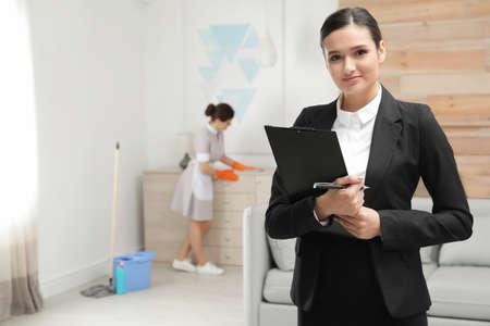Responsabile delle pulizie che controlla il lavoro di pulizia nella camera d'albergo