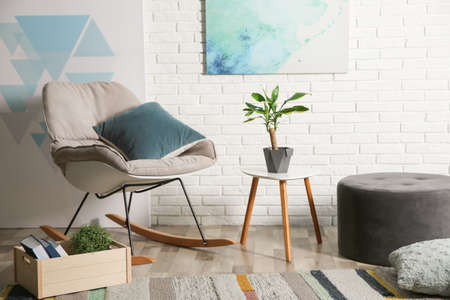 Comfortable rocking chair near brick wall in modern room interior Banco de Imagens
