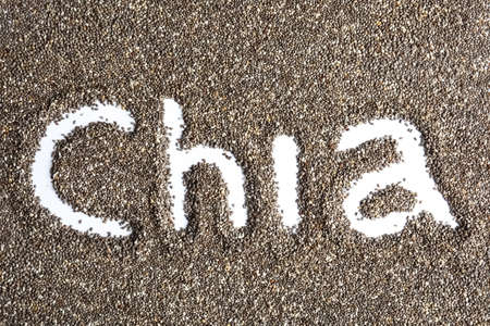 Word CHIA written in seeds on white background, top view