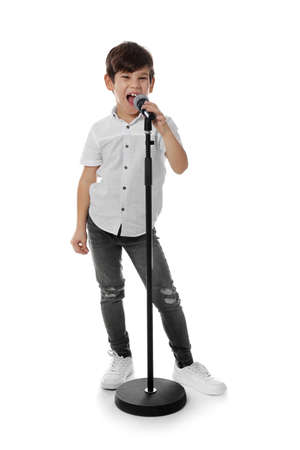 Cute little boy singing into microphone on white background