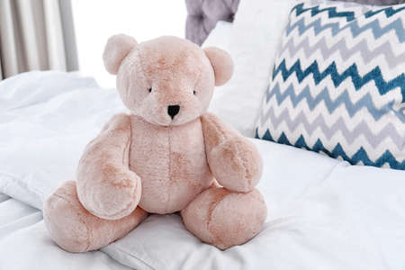 Cute teddy bear sitting on bed indoors. Space for text Stock fotó