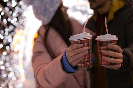 Young couple with cups of mulled wine at winter fair, closeup Foto de archivo