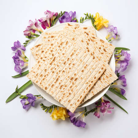 Composition of matzo and flowers on light background, top view. Passover (Pesach) Seder Stock Photo