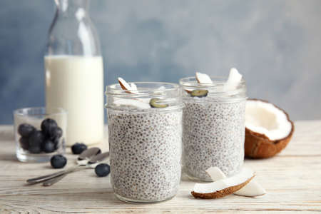 Tasty chia seed pudding with coconut in jars and ingredients on table 免版税图像