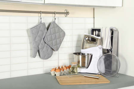 Set of clean cookware, utensils and eggs on table in modern kitchen Imagens