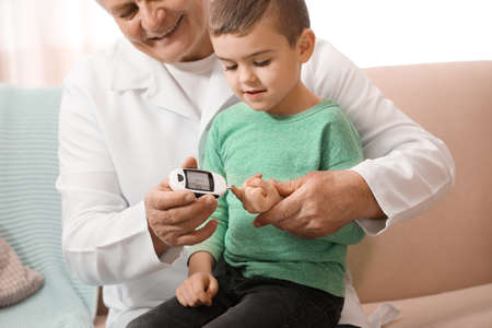 Doctor measuring patient's blood sugar level with digital glucose meter at home. Diabetes control