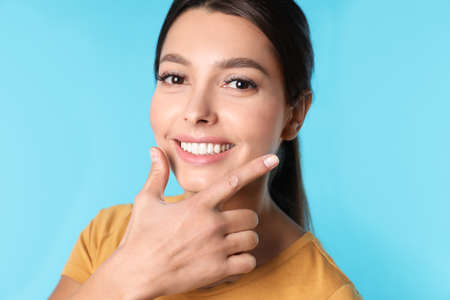 Young woman with healthy teeth on color background Imagens