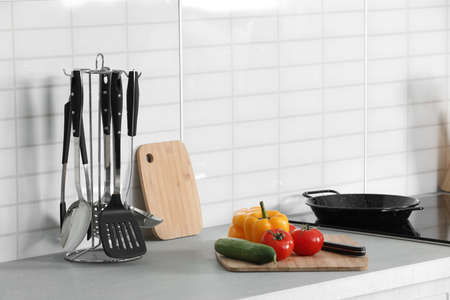 Clean cookware, vegetables and utensils on table in kitchen