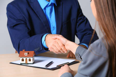 Woman shaking hands with real estate agent at table in office, closeup. Home insurance