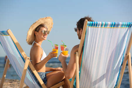 Young couple with cocktails in beach chairs at seacoast