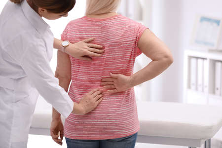 Chiropractor examining patient with back pain in clinic Standard-Bild