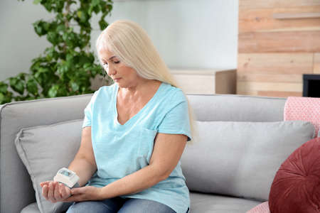 Mature woman checking pulse with medical device at home. Space for text Archivio Fotografico