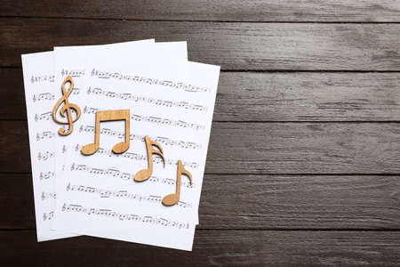 Sheets and music notes on wooden background, top view. Space for text Imagens