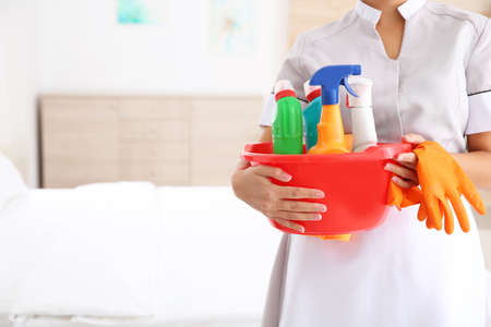 Young chambermaid with cleaning supplies in hotel room, closeup. Space for text Zdjęcie Seryjne