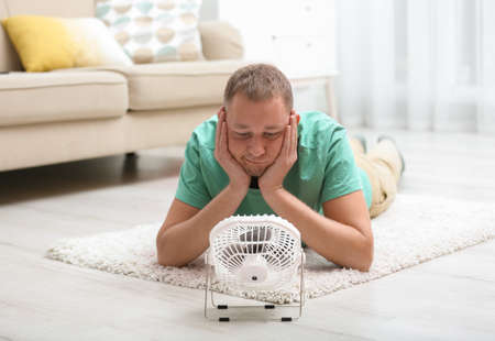 Young man suffering from heat in front of small fan at home