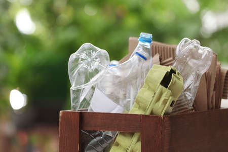 Wooden crate with different garbage on blurred background, closeup. Waste recycling concept Stock fotó
