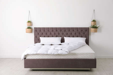 Comfortable bed with new mattress near wall in room. Healthy sleep 免版税图像