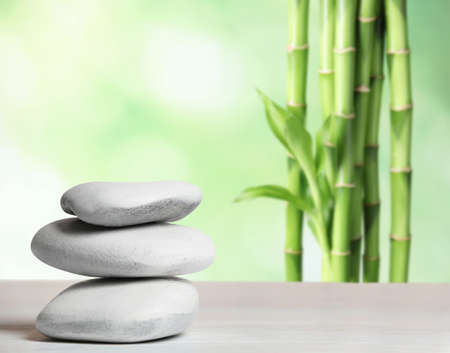 Stack of traditional stones on table against blurred background, space for text. Zen, balance, harmony