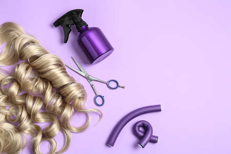 Flat lay composition with hair locks and tools on color background. Space for text